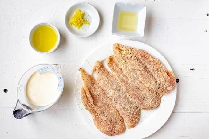 Photo of chicken that has been coated in a Parmesan/Almond flour mixture with small prep bowls containing lemon juice, lemon zest, oil, and heavy cream next to it.