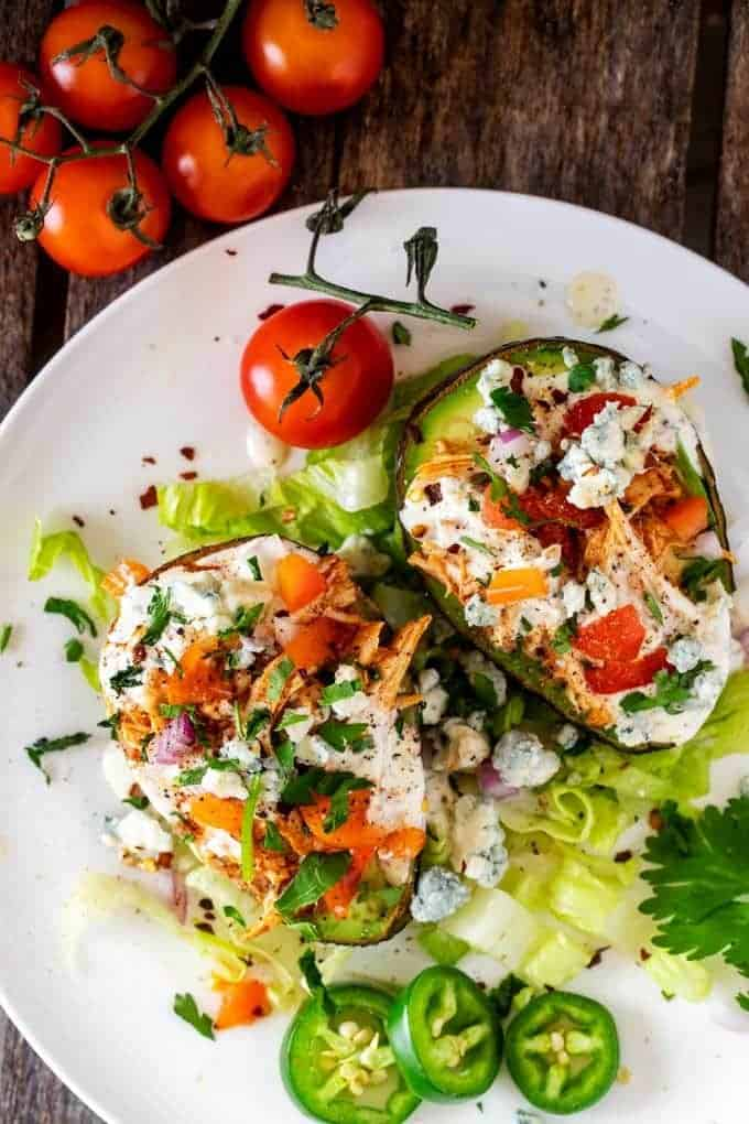 Overhead photo of two avocados stuffed with Keto Slow Cooker Buffalo Chicken and topped with ranch dressing, blue cheese crumbles, tomato, and parsley.