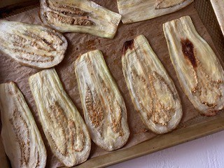 Photo of sliced eggplant in a roasting pan.