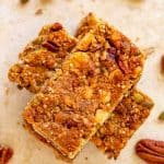 Square overhead photo of three stacked Keto Granola Bars on a travertine background with nuts and seeds scattered around.