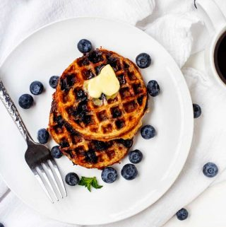 Overhead photo of two Keto Blueberry Chaffles on a white plate surrounded by blueberries.