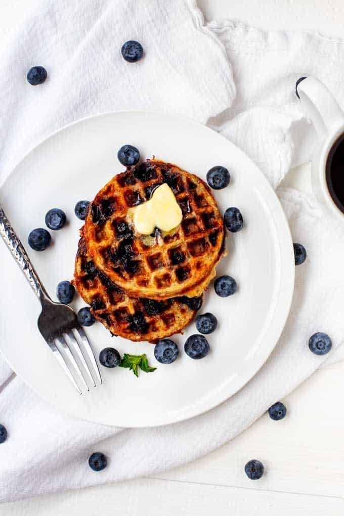 Overhead photo of two Blueberry Chaffles on a white plate with blueberries scattered around.