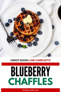 """Overhead photo of a white plate of Blueberry Chaffles with blueberries scattered around and the text """"Crazy Good Low Carb Keto Blueberry Chaffles Below."""""""