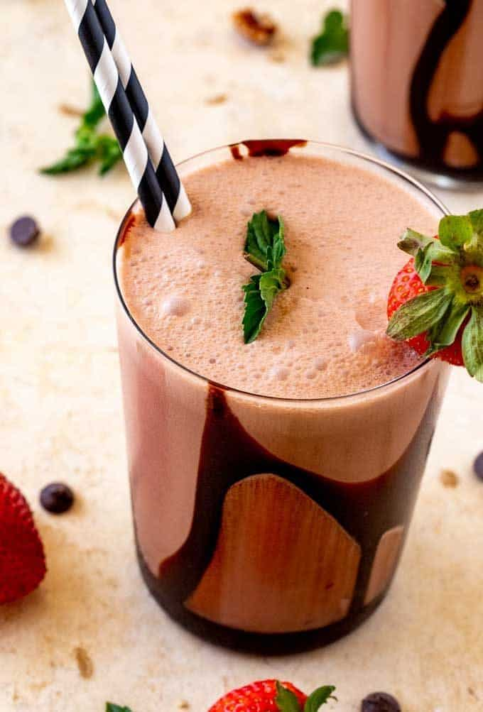 Close up photo of a low carb chocolate smoothie garnished with mint and strawberries.