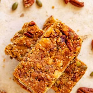 Overhead photo of three stacked Keto Granola Bars on a travertine background with nuts and seeds scattered around.