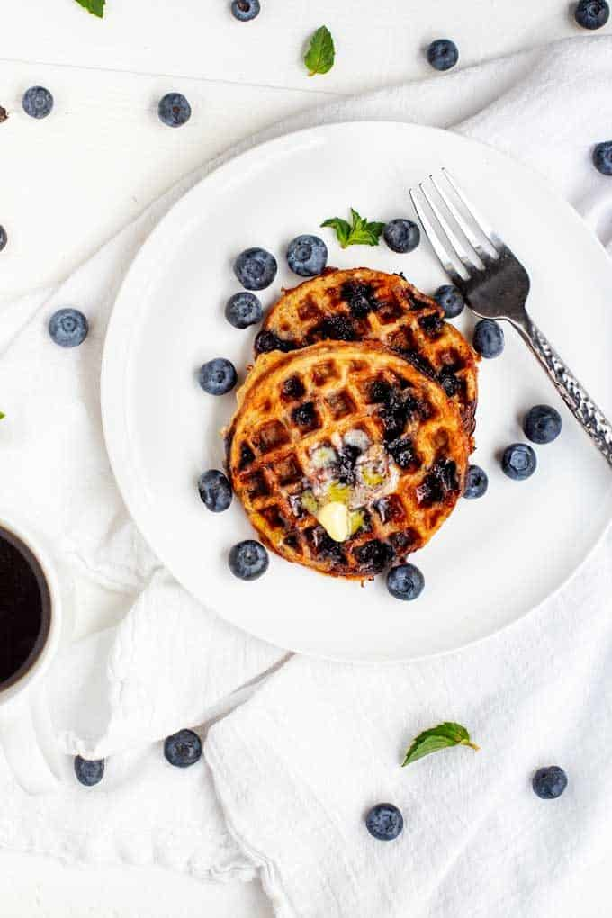 Photo of two blueberry chaffles on a white plate with blueberries scattered around against a white background.