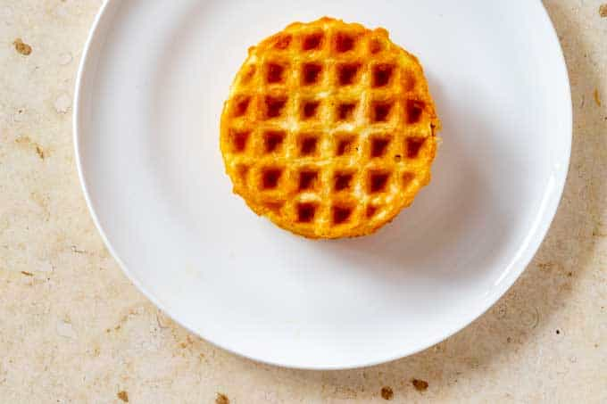 Photo of two plain cooked chaffles stacked on a white plate.