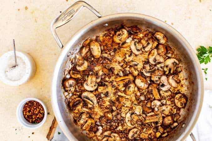 Large skillet with mushrooms cooking in it.