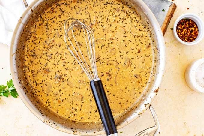 Cream sauce with mushrooms and seasonings in it with a whisk.