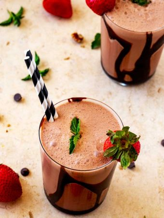 Photo of two glasses of a Keto Chocolate Smoothie garnished with strawberries and mint, with strawberries and chocolate chips scattered around them.