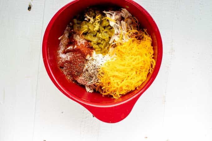 Photo of chicken, sour cream, green chilies, chili powder, garlic, powder, smoked paprika, and cheddar in a red bowl.