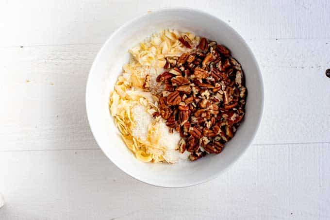 White bowl withe pecans, coconut flakes, and shredded coconut.