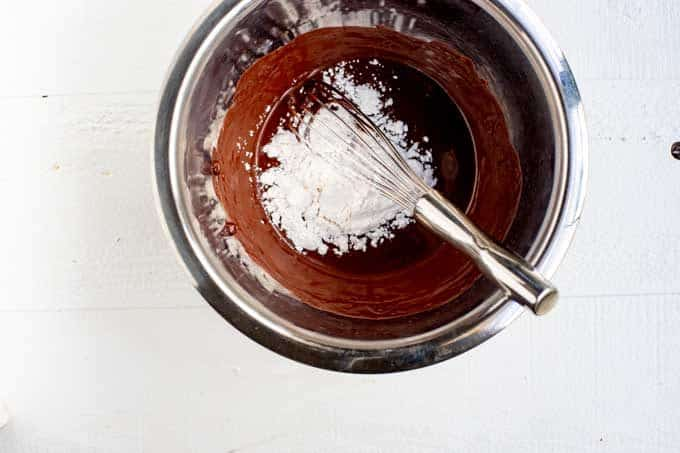 Bowl of swerve being added to melted chocolate.