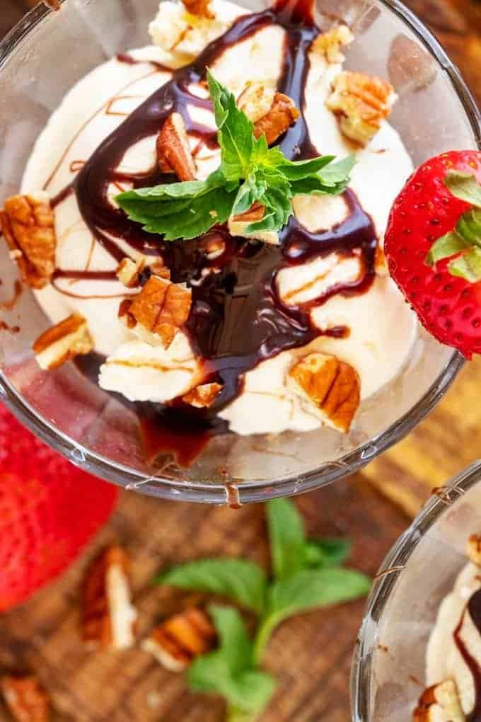 Close Up overhead photo of Keto Vanilla Ice Cream in a glass dish drizzled with chocolate syrup and garnished with pecans, strawberry, and mint.