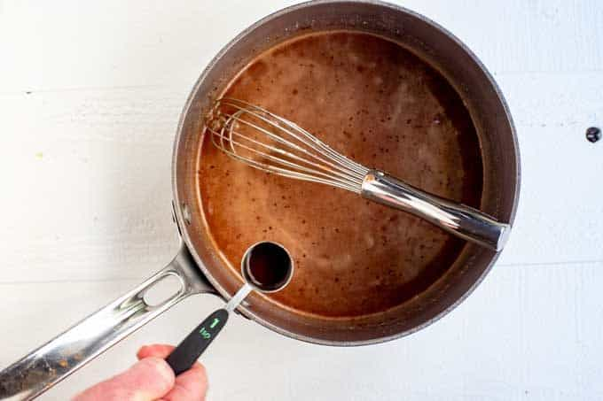 Photo of vanilla being added to a saucepan of coconut oil, peanut butter, cocoa powder, and swerve.