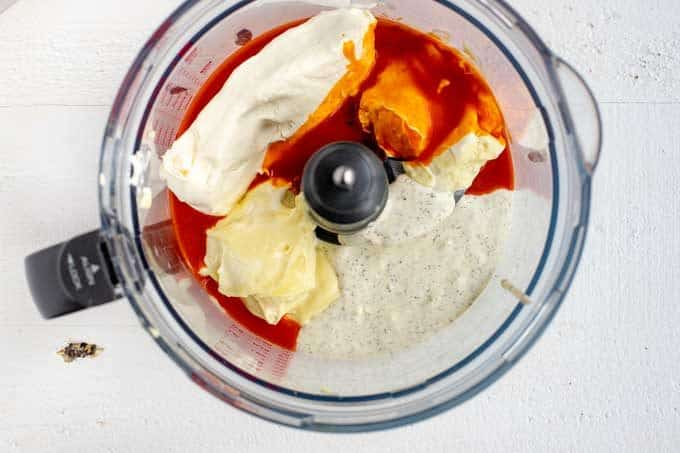 Photo of cream cheese, mayonnaise, ranch dressing, and buffalo sauce in a food processor.