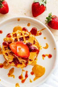 Overhead photo of two stacked keto peanut butter chaffles dusted with sugar-free sweetener with strawberry slices, peanut butter, and stevia sweetened jelly on top.