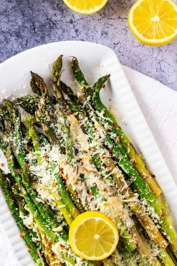 Photo of cheesy Keto Asparagus on a white serving platter with lemon.