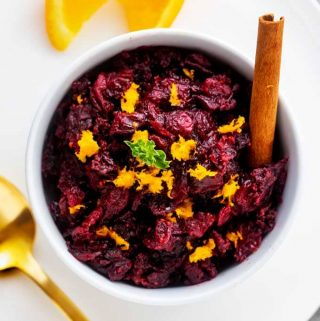 Close up overhead photo of Keto Cranberry Sauce in a white bowl sitting on a white plate with an orange slice and gold spoon next to it.