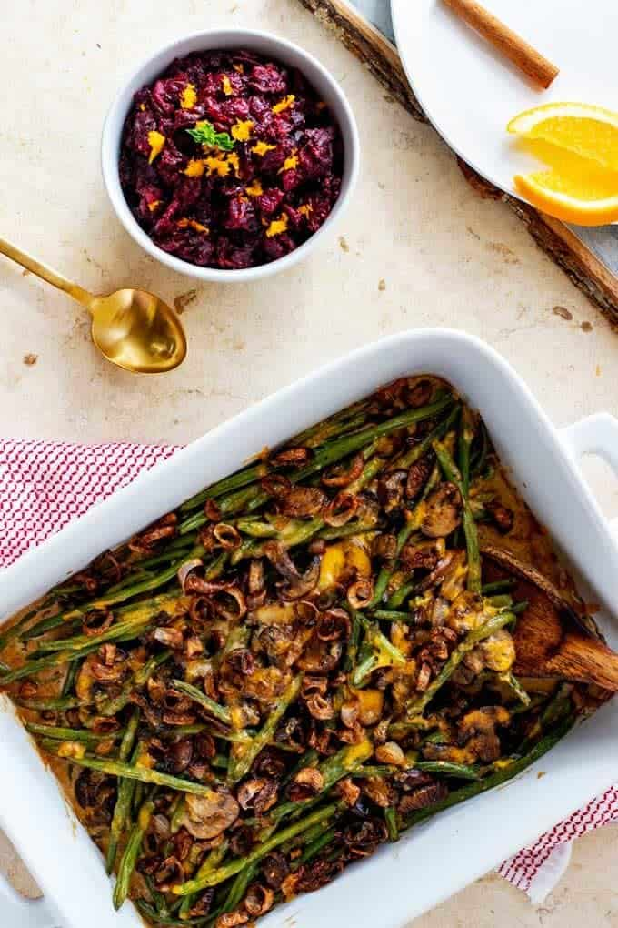 Overhead photo of a Keto Green Bean Casserole in a wide casserole dish with a wooden spoon in it and a bowl of cranberry sauce next to it.