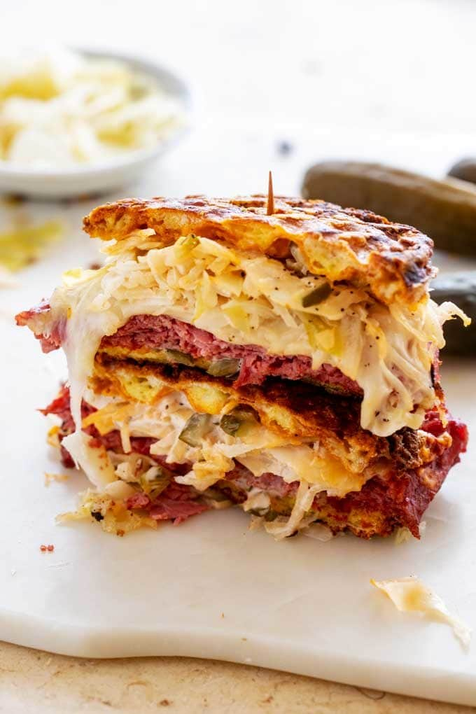 Side photo of a stacked keto reuben sandwich on a white cutting board.