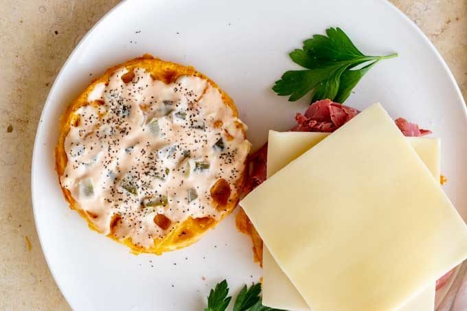 Photo of two chaffles on a white plate.  One has a keto friendly thousand island spread on it and the other has corned beef and cheese slices.