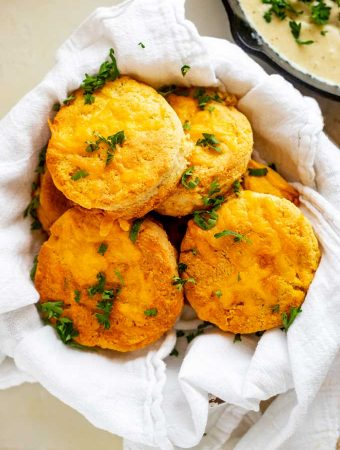 Overhead photo of Keto Biscuits in a cloth lined basket garnished with parsley.