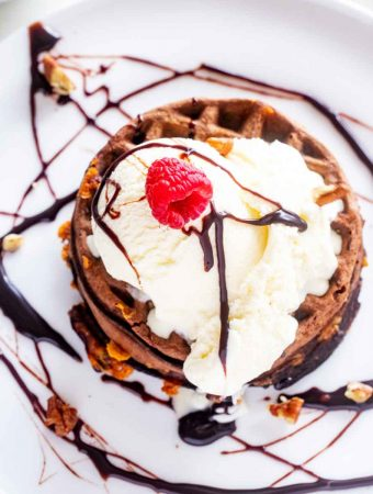 Close-up photo of a Chocolate Chaffle topped with Ice cream, chocolate syrup, pecans, and a raspberry.