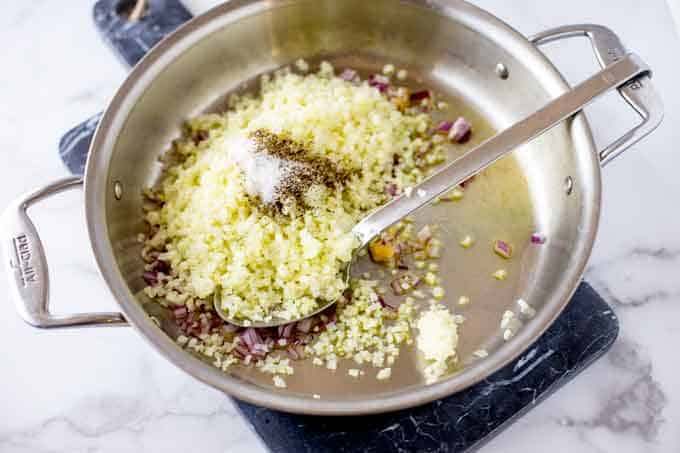 Photo of onion, garlic, cauliflower rice, and seasonings in a skillet with a spoon.