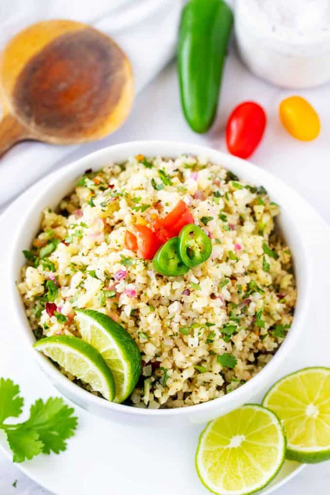 Overhead photo of a bowl of cilantro lime cauliflower rice garnished with tomato, lime, and jalapeno.