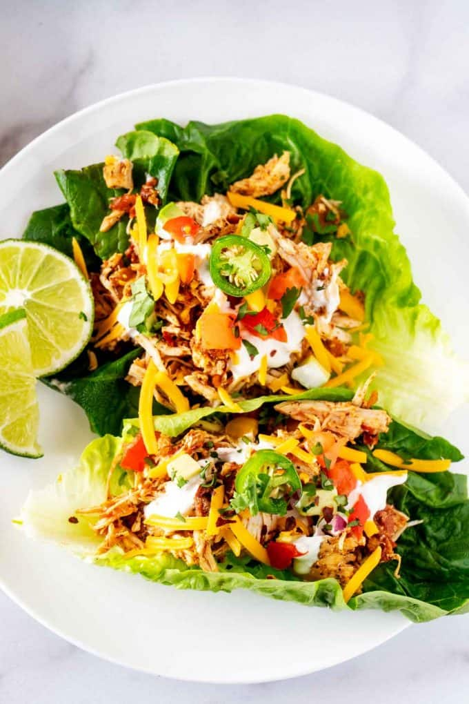 Overhead photo of Chicken Taco Lettuce Wraps on a white plate with a lime garnish.