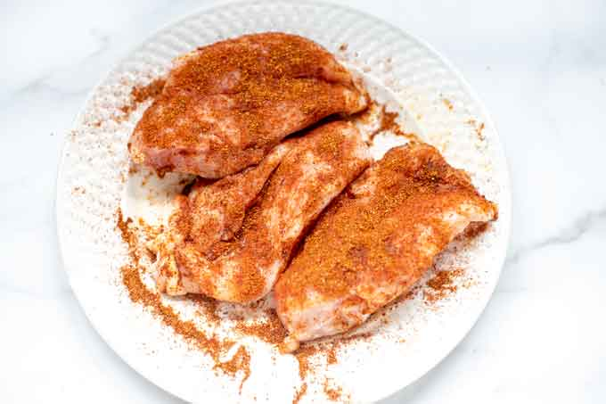 Photo of chicken breast sprinkled with seasoning.