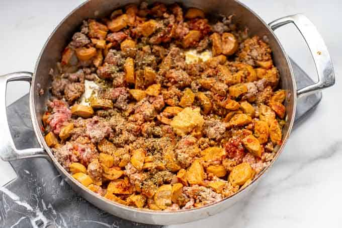 Photo of ground beef, sausage, garlic, onions, and seasonings in a skillet.
