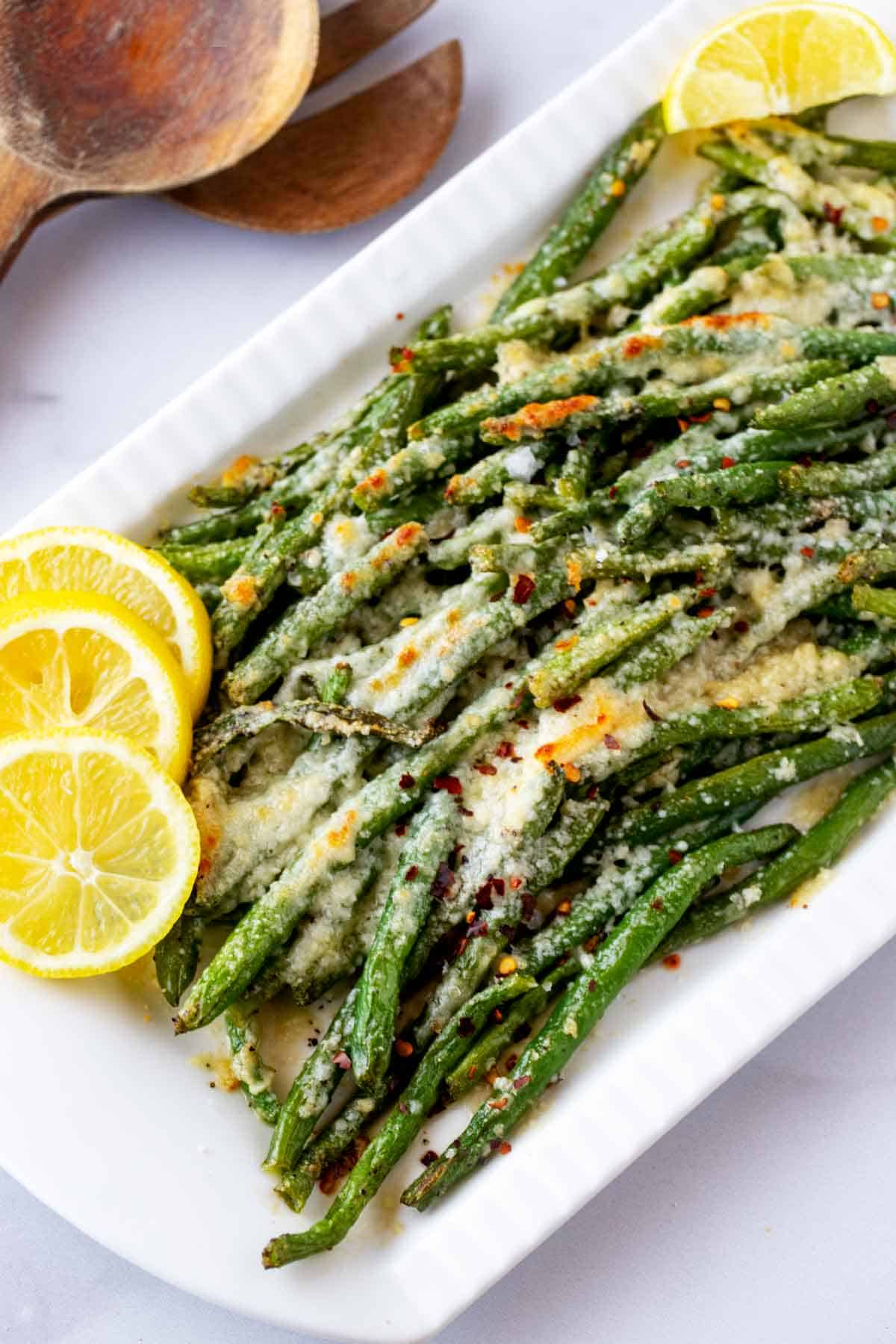 3/4 overhead photo of Roasted Green Beans with Parmesan on a white platter garnished with lemons.