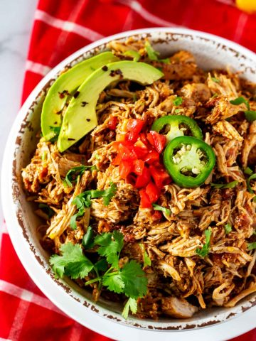 Close up photo of a white bowl of Slow Cooker Chicken Tinga garnished with tomato, cilantro, avocado, and jalapeno.