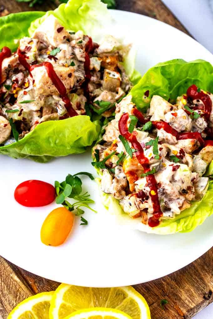 Photo of two lettuce cups with Keto Chicken Salad with Bacon on a white plate with a drizzle of hot sauce.