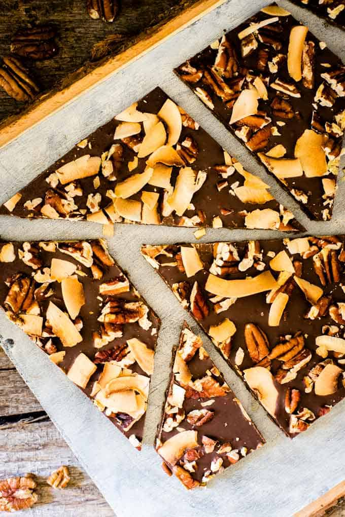 Close up photo of Keto Chocolate Bark on a rustic cutting board against a dark background.