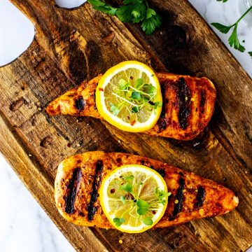 Overhead square photo of marinated chicken on a wooden cutting board garnished with lemons and microgreens.