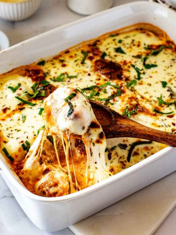 Square photo of a meatball casserole in a white casserole dish with a wooden spoon scooping out a meatball with stringy cheese.