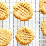 Square overhead photo of keto peanut butter cookies on a cooling rack against a white background.