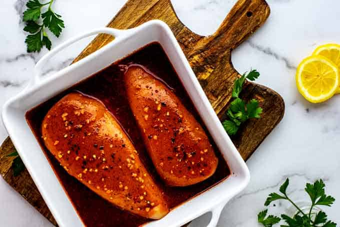 Photo of two chicken breasts in a white casserole dish covered by Keto Chicken Marinade.