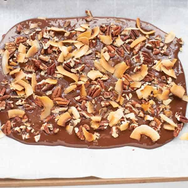 Photo of melted sugar-free chocolate on a parchment lined baking sheet sprinkled with toasted coconut and pecans.