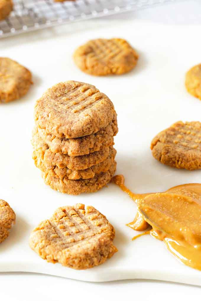 Side photo of four stacked keto peanut butter cookies surrounded by other cookies against a white background.
