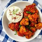 Square overhead photo of BBQ Cauliflower Wings on a white plate with a small dish of ranch dressing beside it.