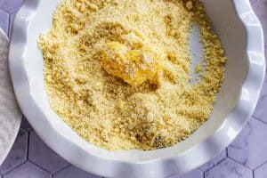 Photo of a piece of cauliflower that has been dipped in an egg wash being coated with an almond flour parmesan cheese mixture.