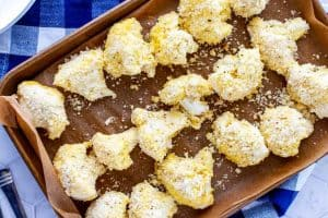 Photo of a parchment lined sheet pan with cauliflower pieces that have been coated with a parmesan cheese and almond flour mixture.