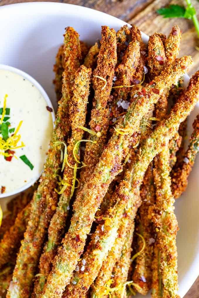 Close up photo of Keto Asparagus Fries on a white plate with lemon aioli sitting next to it.