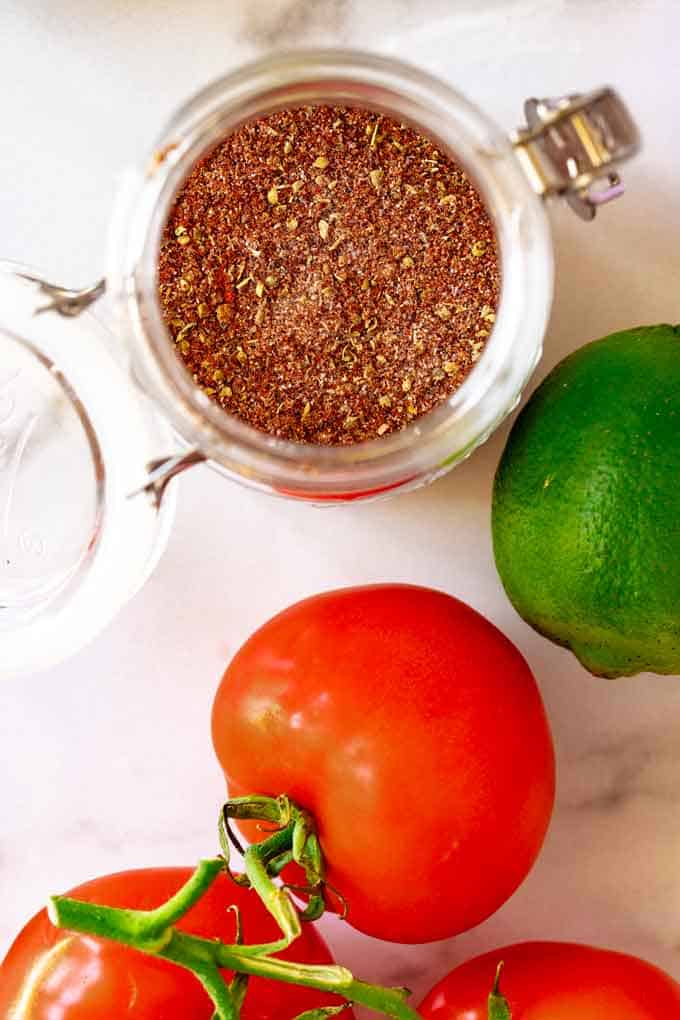Overhead photo of a small jar of keto taco seasoning surrounded by lime and tomato.
