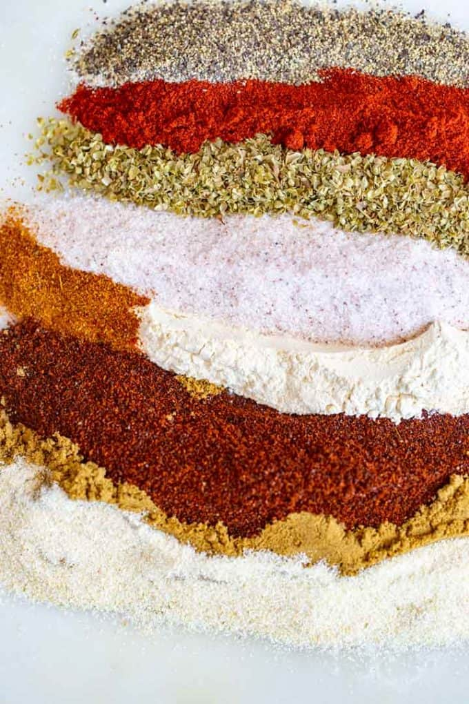 Ingredients for taco seasoning on a white cutting board.
