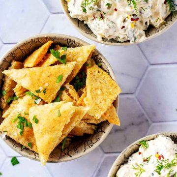 Square photo of keto tortilla chips in a small bowl on a white tile background with two bowls of dip sitting next to them.